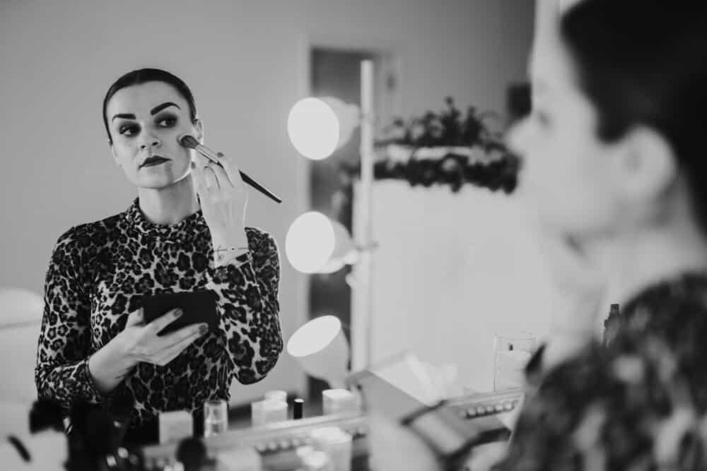 mulher a maquilhar-se em frente ao espelho